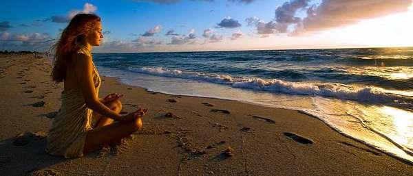 Женщина медетирует на берегу