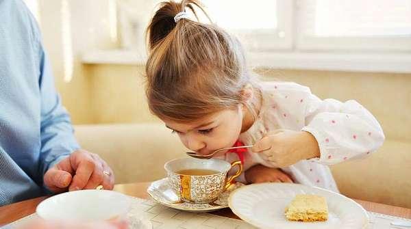 Ребенок пьет из ложки чай