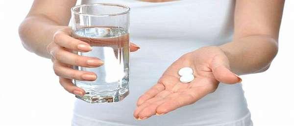 Женщина с двумя таблетками и стаканом воды в руках