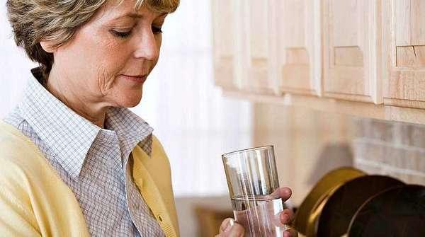 Женщина пьет таблетки