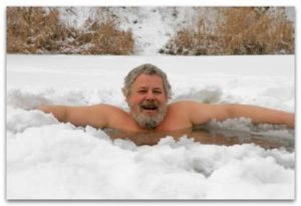 Пожилой мужчина купается в проруби