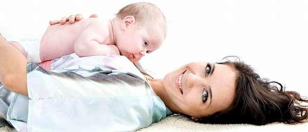Улыбающаяся девушка с грудным ребенком