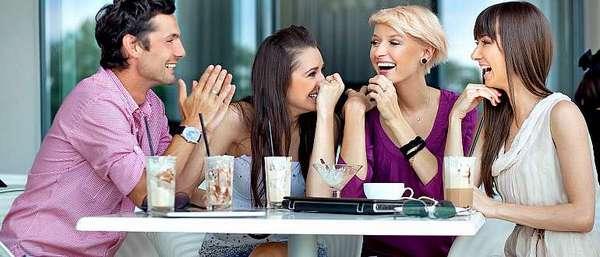 Женщины весело беседую и смеются с мужчиной