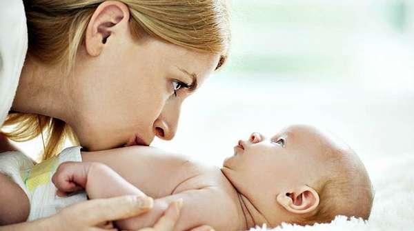 Мама целует в живот грудничка