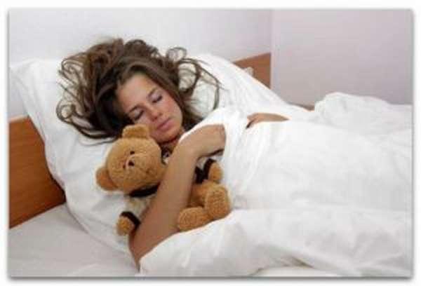 Девушка спит с плюшевым медведем