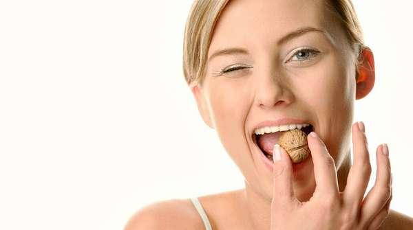 Девушка ест грецкий орех