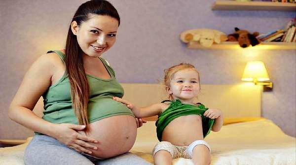 Беременная девушка с дочкой