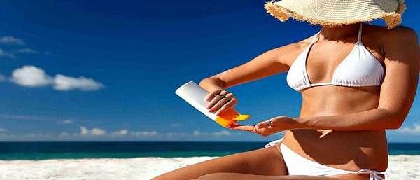 Женщина мажется кремом для защиты от солнца