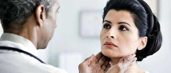 Врач проверяет щитовидную железу у пациентки